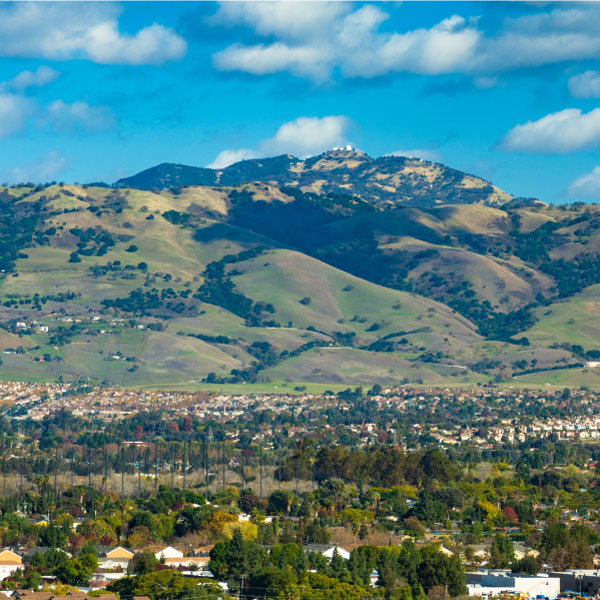 View overlooking Santa Clara Valley with residences in the foreground and green hills in the distance with clouds dotting the blue sky above.