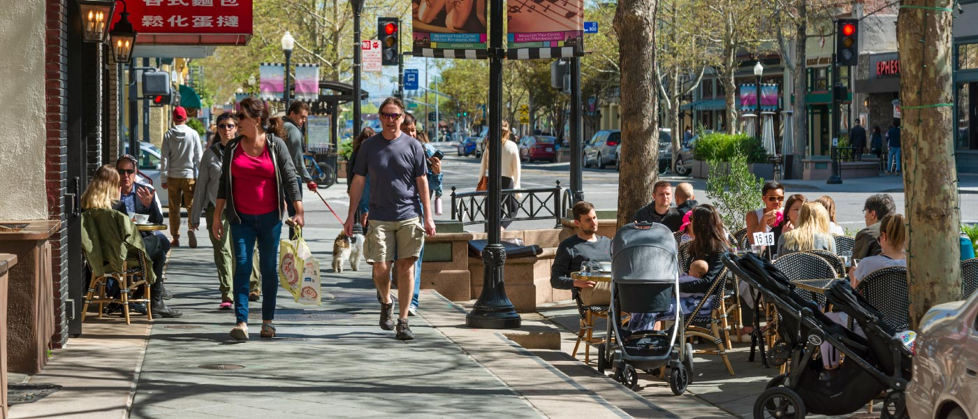 A busy neighborhood retail district with people enjoying sidewalk dining, pushing strollers, and walking dogs.