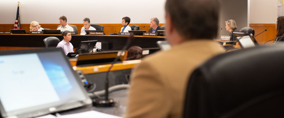 A commission meeting with commissioners seated at desks.