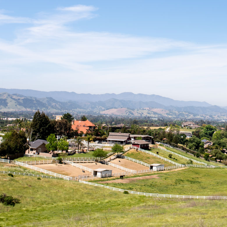 Rural community with fencing and ranch homes on green hills.